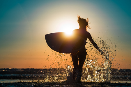 Woman runs into ocean with surf board and lots of splashes Zdjęcie Seryjne