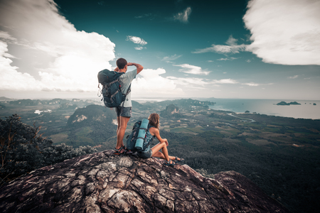 Hikers relax on top of a mountain and enjoy valley view