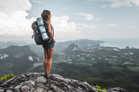 Hiker stands on top of a mountain and enjoys valley view