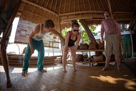 방갈로에서 호흡 운동을하는 젊은 사람들의 그룹 스톡 콘텐츠