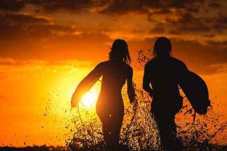 Couple of surfers run with boards and lots of splashes at sunset photo