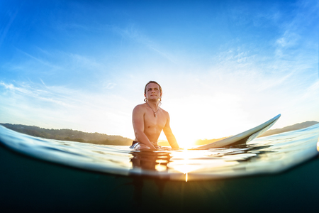 Young man sits on the surfboard in the ocean and waits wave during his sunrise surf session photo