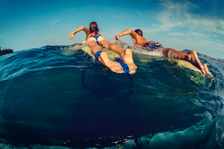 Couple of surfers paddles on the surf board in the ocean photo