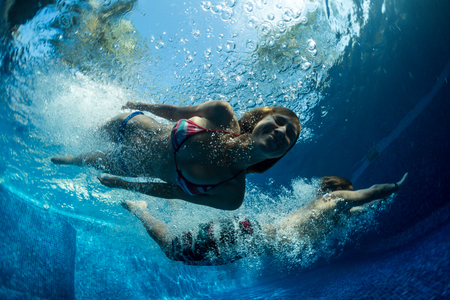 Underwater shot of the couple jumping in the pool Stock Photo