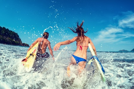 Couple of surfers run with boards and lots of splashes photo