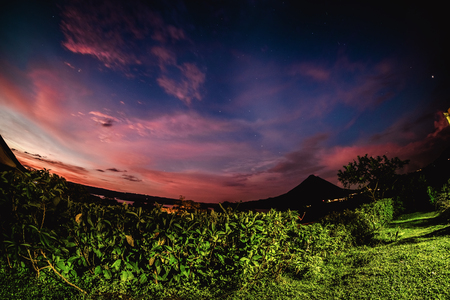 Volcano of Arenal at the night with green bush on the foreground