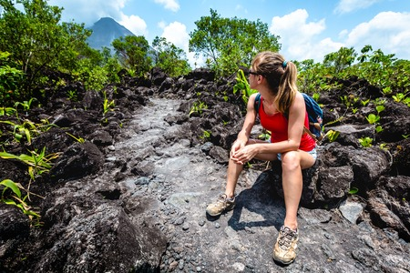 Young woman hiker relaxing on the hard and rocky lava trail with volcano on the horizon