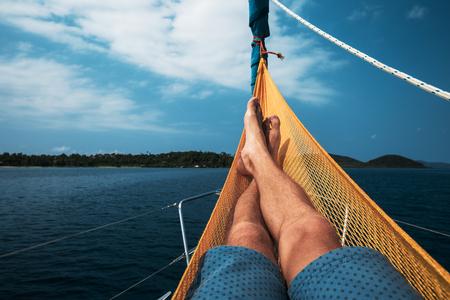 男がヨットに設定ハンモックでリラックスします。