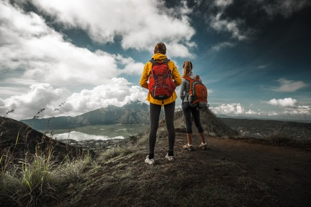 Two hikers stand on a hill and enjoy valley view