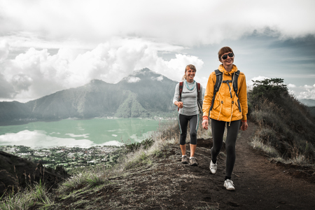 Two young smiling women hikers walk in mountains Stock Photo