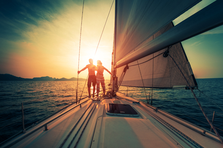 cordage: Young couple enjoys sunset from the sailing boat moving in the tropical sea