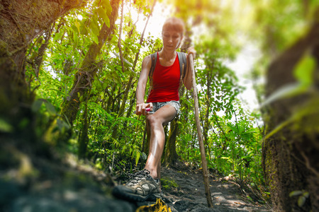 Young woman hiker applying mosquito repellent in dense tropical forest. Tilt shift effect used Stock Photo