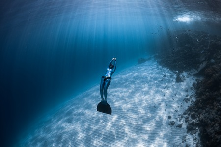 Woman freediver glides over sandy bottom of a crystal clear tropical sea Stock Photo
