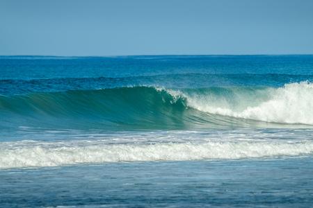 Blue power wave breaking in the shore