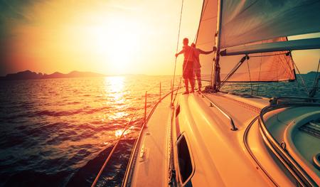 若いカップルは、熱帯の海で航行ボートからの夕日を楽しむ