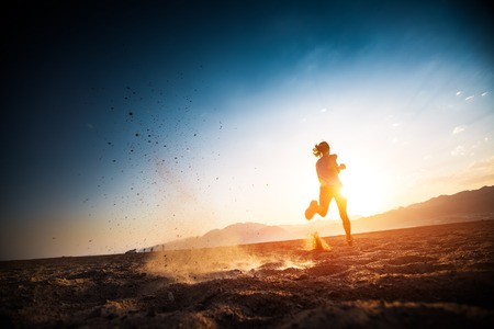 Woman runs on the desert with lots of dust