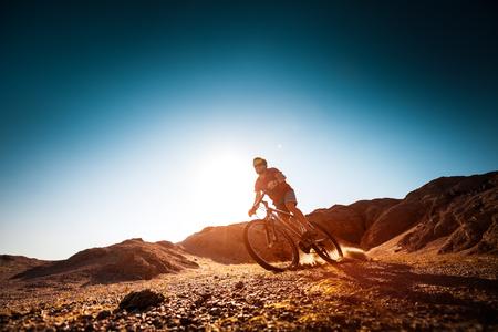 off road biking: Man rides bicycle in the dry desert terrain