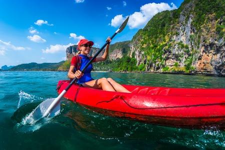 여자 열 대 바다에서 빨간 카약 paddles