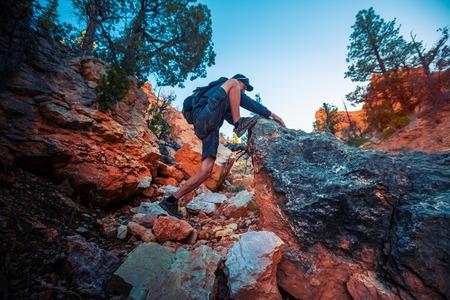 Hiker climbs steep rock in the wild Banco de Imagens