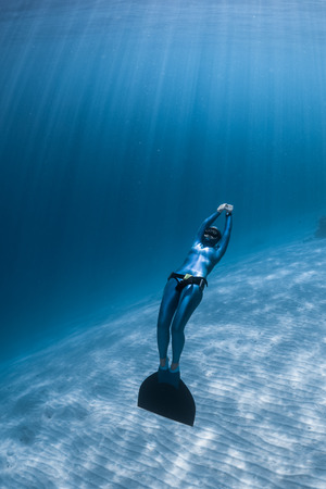 Woman freediver relaxes underwater with monofin over sandy bottom