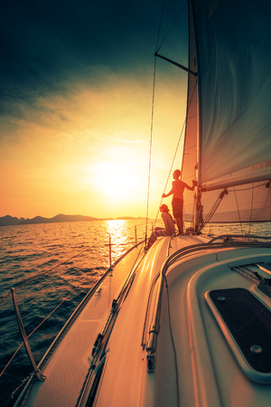 Young couple enjoys sunset from the sailing boat moving in the tropical sea
