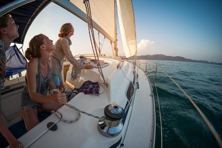3 人の若い女性は、熱帯の海の穏やかなエリアで入力した後ジェノヴァ帆を調整します。 写真素材
