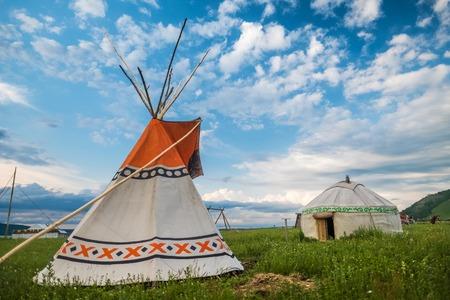 Teepee e yurt set no prado verde com céu azul no fundo Foto de archivo - 83938018