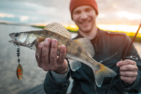 Happy fisherman holds the fish