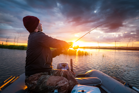 Man fishing on the lake from the boat at sunset Stock Photo