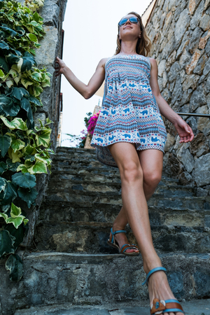 Woman in summer dress walks down the tiled stairs