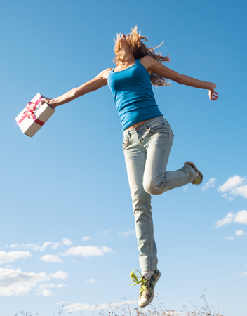 Young woman jumps with present box over blue sky background photo