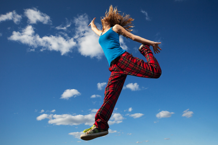 Young woman jumps over blue sky background photo
