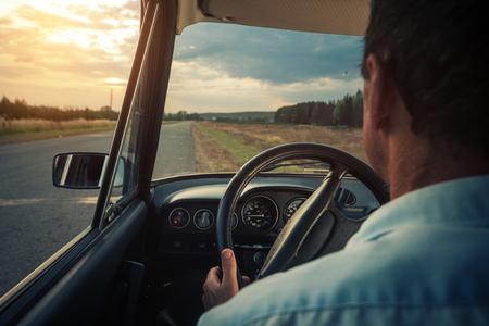 Senior man zit in een auto op een landelijke lege weg met rode brandstof lamp verscheen op het dashboard Stockfoto