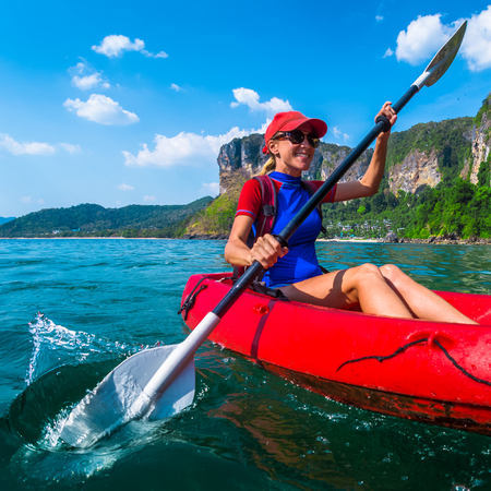 Woman paddles red kayak in a tropical sea