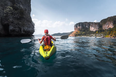 Woman paddles kayak in a calm sea among the tropical islands