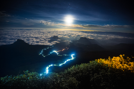 Illuminated path to the top of the mountain of Adams Peak with moon and stars in the sky. View from Adams Peak, Sri Lanka