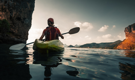 Woman paddles kayak in the calm sea among the islands