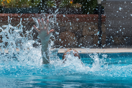 Person drowns in the pool with splashes Stock Photo