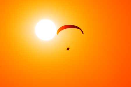 Paraglider flies against the sun