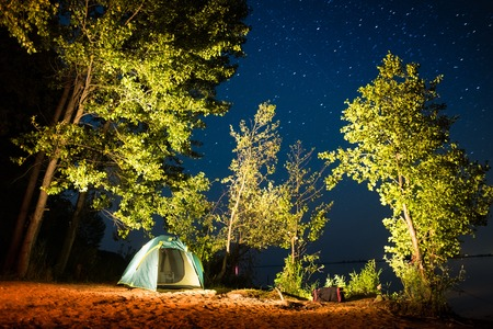 Tent set among the hightlighted trees on coast of a river with stars in the night sky