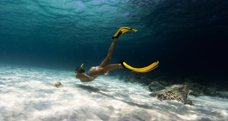 Woman freediver explores tropical underwater world, glides over sandy bottom among the rocks Stock Photo