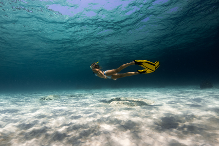 Woman freediver explores tropical underwater world, glides over sandy bottom Stock Photo