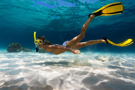 Woman freediver explores tropical underwater world, glides over sandy bottom on a breath hold