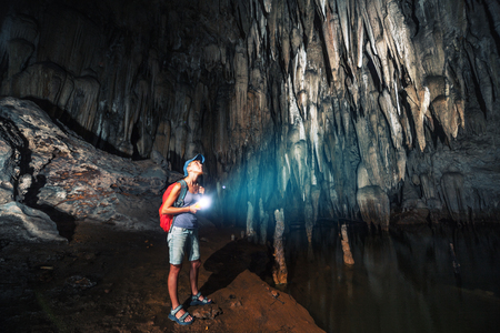 Young woman explores cave with stalagmites and stalactites Imagens - 85199390