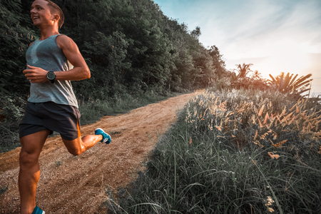 Athletic happy man runs on a rural tropical road during sunset