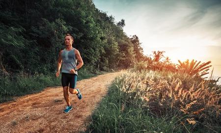 L'homme athlétique court sur une route tropicale rurale pendant le coucher du soleil Banque d'images - 85362079