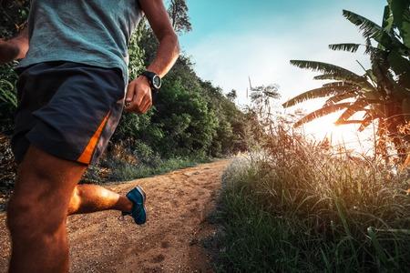 L'homme athlétique court sur une route tropicale rurale pendant le coucher du soleil Banque d'images - 85386178