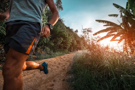 L'homme athlétique court sur une route tropicale rurale pendant le coucher du soleil Banque d'images - 85386357