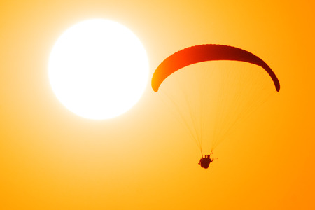 Paragliders in tandem fly against the sun and take selfie picture Zdjęcie Seryjne