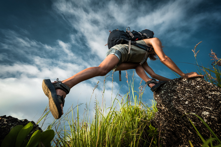 Tourist with backpack climbing a steep rock over blue sky background Stock Photo